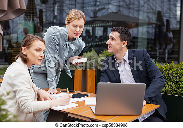 Blonde-haired businesswoman wearing stylish blouse joining staff meeting - csp58334908