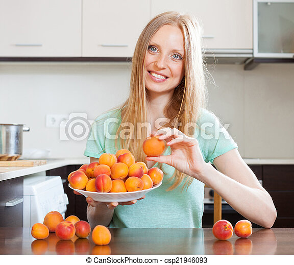 blonde long-haired girl holding apricots in home kitchen - csp21946093