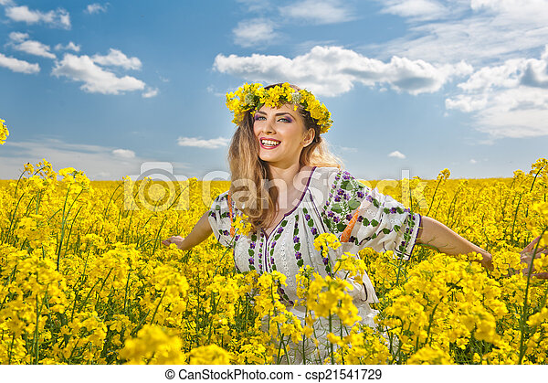 Blonde smiling in canola field - csp21541729