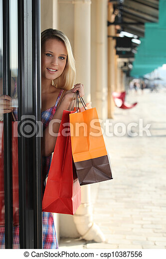 blonde woman entering in a store - csp10387556