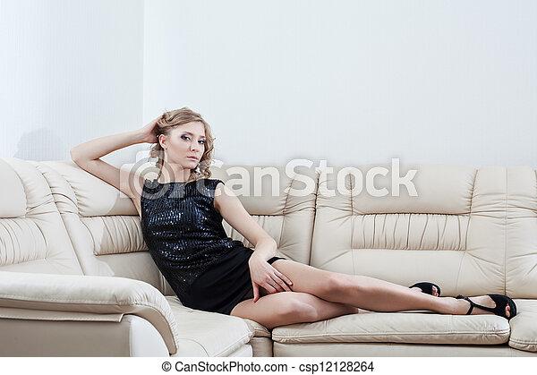 Blonde woman in black dress sitting on sofa - csp12128264