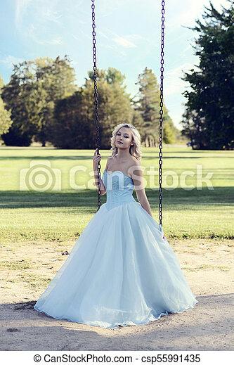 Portrait of blonde woman in blue dress playing on swing.