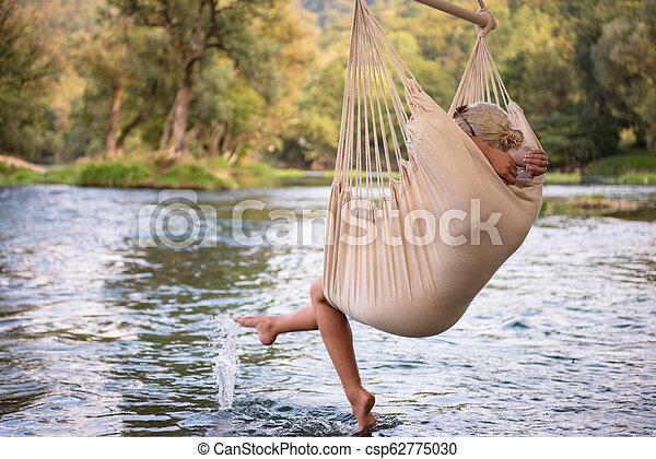blonde woman resting on hammock - csp62775030