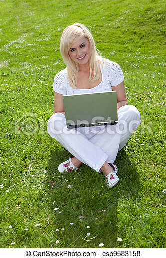 Blonde woman using a laptop on the grass - csp9583158