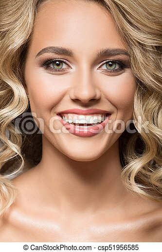 Blonde woman with curly hair smiling. Close up portrait. - csp51956585