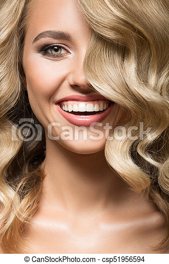 Blonde woman with curly hair smiling. Close up portrait. - csp51956594