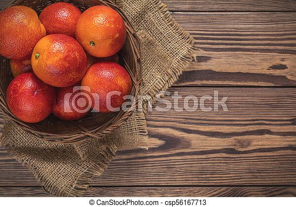 Blood orange fruit in a wicker basket on dark wooden table. - csp56167713