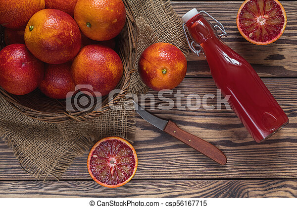 Blood orange fruit in a wicker basket and bottle juice on dark wooden table. - csp56167715