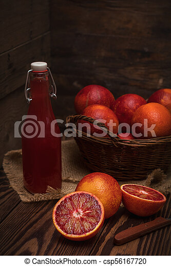 Blood orange fruit in a wicker basket and bottle juice - csp56167720