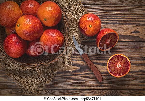 Blood orange fruit in a wicker basket and bottle juice - csp56471101
