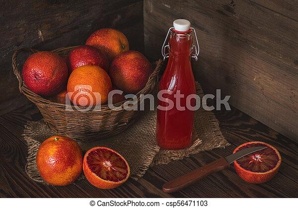 Blood orange fruit in a wicker basket and bottle juice - csp56471103
