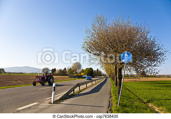 blossoming tree at a street with bicycle lane - csp7638430