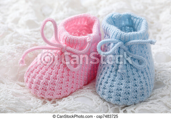 bcf1551132f5 Blue and pink baby booties on white background.