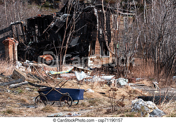 Blue baby carriage near old wooden burned-down house - csp71190157