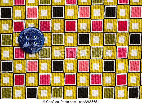 blue button on colourful fabric  - csp22665651