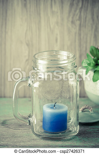 Blue candle in bottle glass - csp27426371