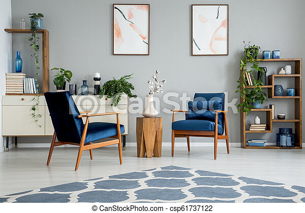 Blue carpet in grey living room interior with posters and wooden table between armchairs. Real photo - csp61737122
