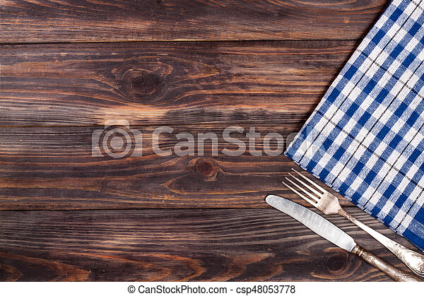 blue checkered tablecloth on the black wooden table with copy space for your text. Top view - csp48053778