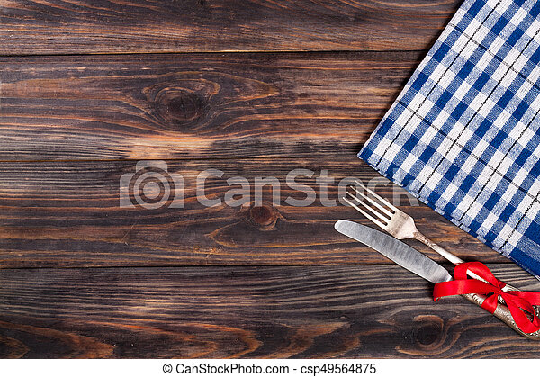 blue checkered tablecloth on the black wooden table with copy space for your text. Top view - csp49564875
