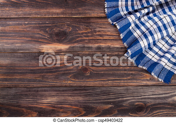 blue checkered tablecloth on the black wooden table with copy space for your text. Top view - csp49403422