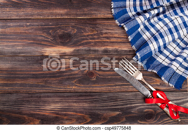 blue checkered tablecloth on the black wooden table with copy space for your text. Top view - csp49775848
