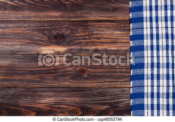 blue checkered tablecloth on the black wooden table with copy space for your text. Top view - csp48053794