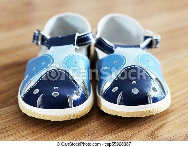 Blue child's sandals on wooden background - csp55928387