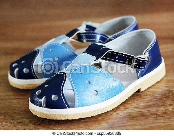 Blue child's sandals on wooden background - csp55928389