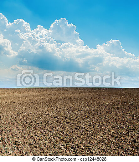blue cloudy sky and black plowed field - csp12448028