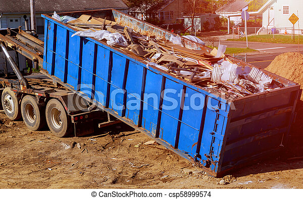 Blue construction debris container filled with rock and concrete rubble. Industrial garbage bin - csp58999574