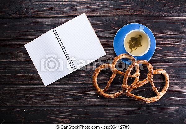 Blue cup with fresh pretzels - csp36412783
