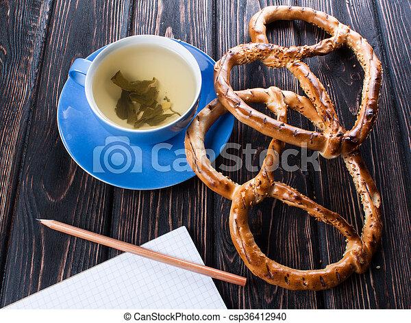 Blue cup with fresh pretzels - csp36412940