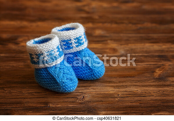 Blue hand made crochet baby booties on wooden background, copyspace - csp40631821