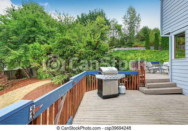Blue House exterior. Walkout deck with barbeque and patio set - csp39694248