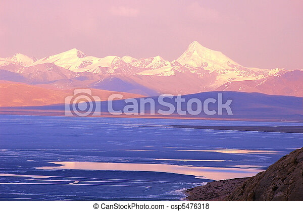 Blue lake and snow mountains at sunrise - csp5476318