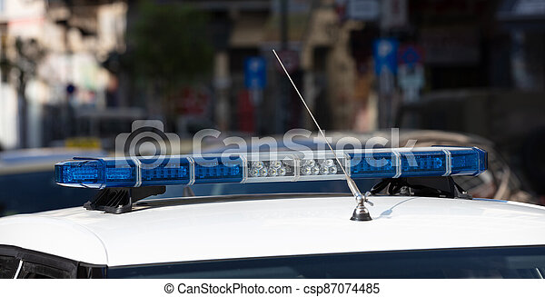 Blue light flasher at police car top, defocused city street background - csp87074485