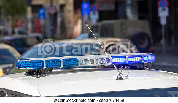 Blue light flasher at police car top, defocused city street background - csp87074469