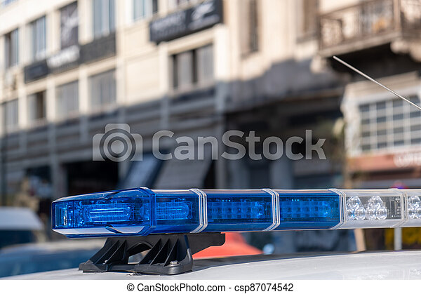 Blue light flasher at police car top, defocused city street background - csp87074542