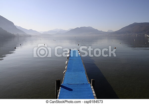 Blue pontoon and view of annecy lake and mountains on winter morning - csp9184573