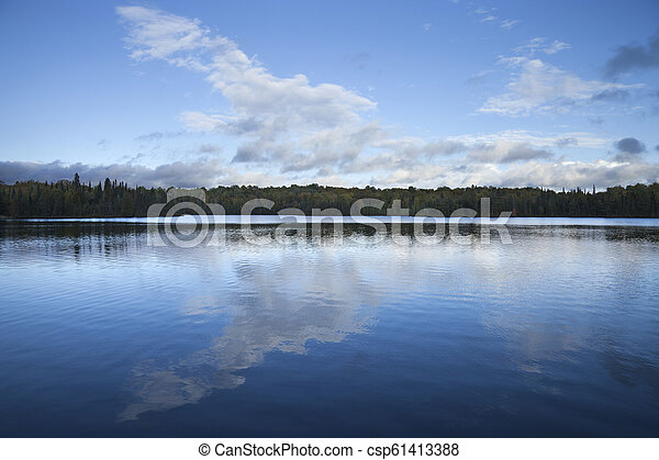 Blue sky and clouds over calm lake at dusk in northern Minnesota - csp61413388