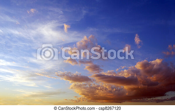 Blue sky approaching to sunset time, with fluffy clouds tinted in orange. - csp8267120