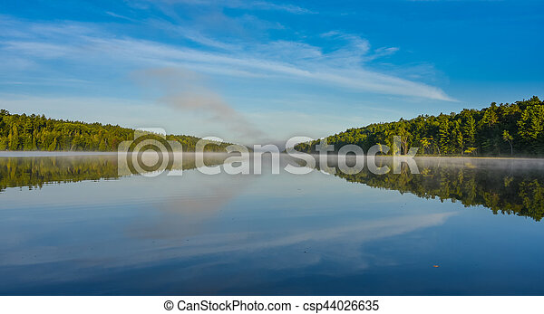 Blue sky misty summer morning in middle of Corry lake. - csp44026635