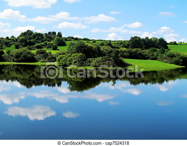 blue sky of Ireland with forests and green meadows and reflections on the clear water - csp7524318
