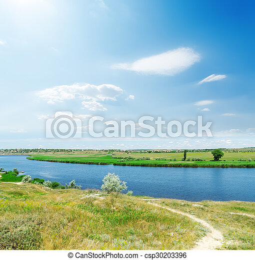 blue sky with clouds and sun over river - csp30203396