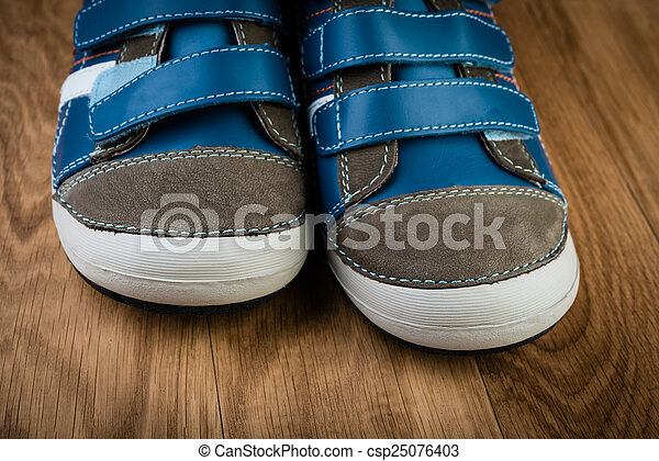blue sneakers on wooden background - csp25076403