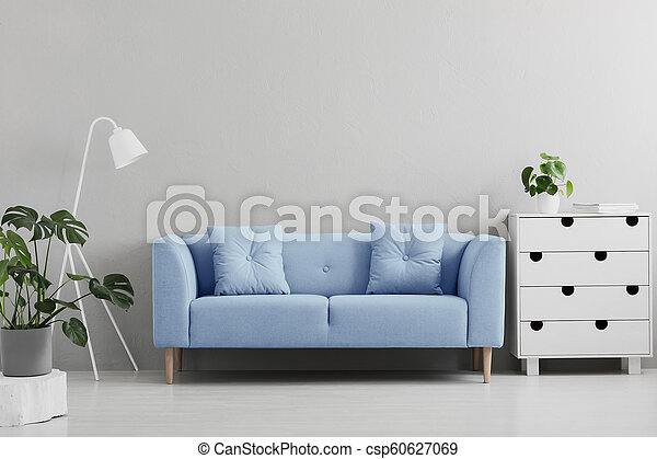 Blue sofa between white lamp and cabinet in grey living room interior with plants. Real photo - csp60627069