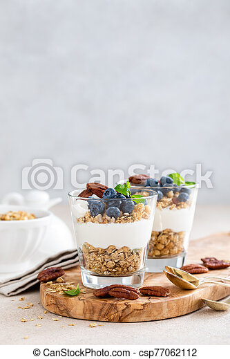 Blueberry layered parfait with ricotta cheese, granola and pecan nuts - csp77062112