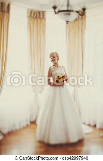 Braut mit einem Strauß gelber und roter Blumen posieren vor einem Fenster - csp42997940