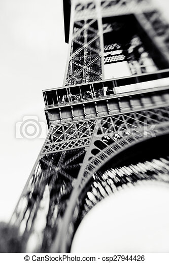 Blurred shot of the Eiffel Tower in Paris, France, selective focus on details. Lensbaby photo of Eiffel Tower, vintage black and white colors - csp27944426