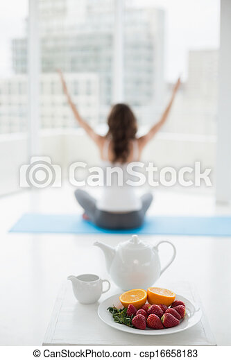Blurred toned young woman sitting in meditation posture with healthy food in foreground at fitness studio - csp16658183